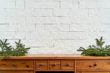 Christmas decoration with blank space with twigs of spruce on an old shelf on the background of a white brick wall