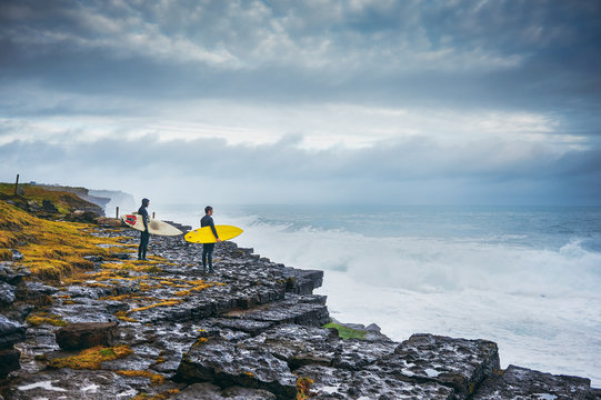 Surfers looking at the stormy ocean from the cliff