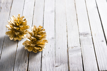 golden pine cones Christmas decoration on old rustic wooden table background