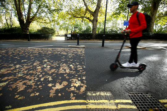Man on a scooter wheels along a road, where the fallen autumn leaves have made a pattern, in central London