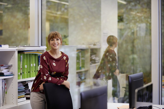 Portrait Of Smiling Businesswoman Leaning On Chair