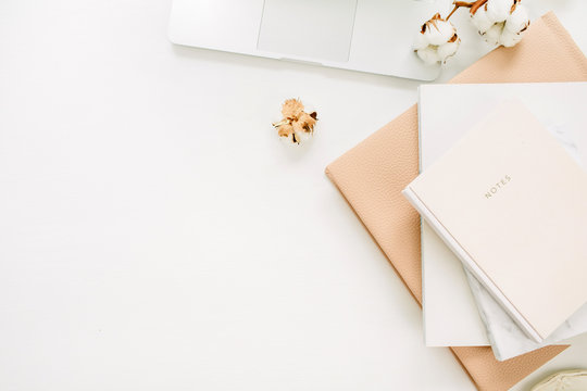 Laptop, notebook, cotton branch on white background. Flat lay, top view minimal home office desk workspace.