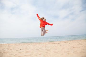 joyful woman jumping on a sandy beach, Ocean