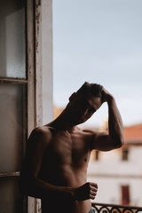 handsome man bare chest posing on a window