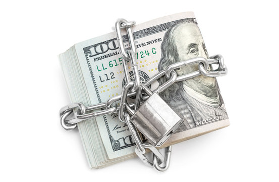 Folded dollar bills bound by metal chain with padlock. Business concept.
