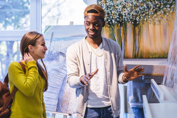 Young attractive couple standing close to one and other in an art gallery looking at a framed work, black hipster man and european student woman talking, choocing, buying souvenirs in gift shop.