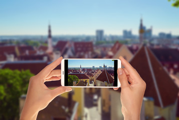 A tourist is taking a photo of Tallinn from the top in a clear sunny day on a mobile phone