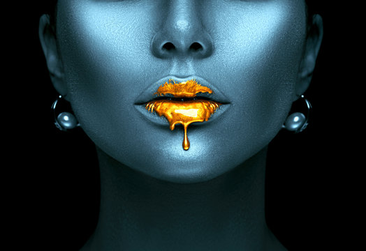 Gold paint drips from the sexy lips, golden liquid drops on beautiful model girl's mouth, creative abstract dark blue skin makeup. Beauty woman face
