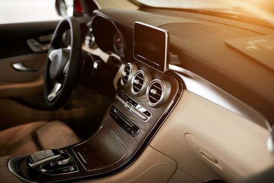 Luxury car interior steering wheel and dashboard close up. Beige leather salon, wood decoration, new edition