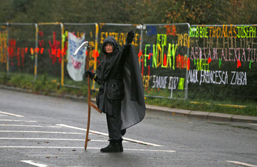 A protester stands outside Cuadrilla's Preston New Road fracking site near Blackpool