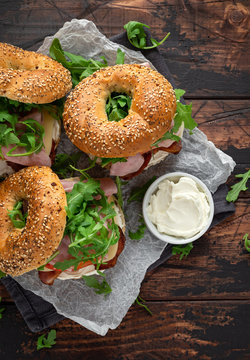 Fresh Bagels Sandwiches with cream cheese, bacon, tomato and green wild rocket on rustic wooden table