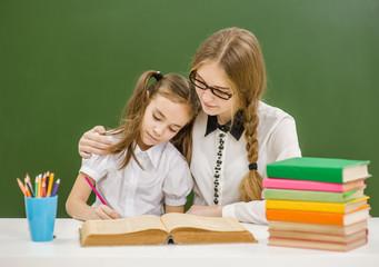 Teacher hugs a little sad girl at school
