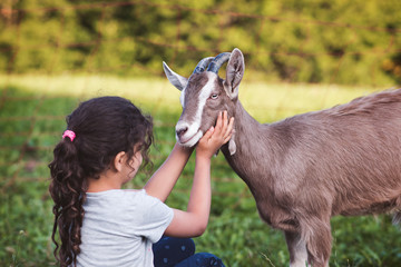 Child gently hugging a goat
