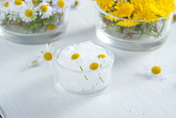 cosmetic product samples with herbal flowers on white wooden table