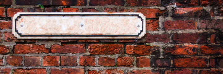 Panoramicz photo of a wall from a red old brick with a white rusty mockup plaque