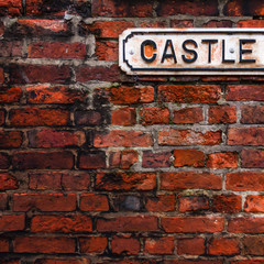 A white rusty plate with the word CASTLE on the background of a wall made of old red brick