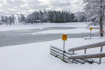 Ice covered lake with a warning sign for thin ice