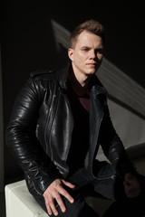 fashion portrait of a man in black fancy leather jacket
