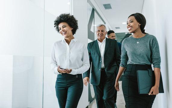 Team of corporate professionals in office corridor