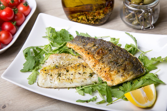 Grilled seabass fillet with arugula, lemon, tomatoes and capers. Close-up.