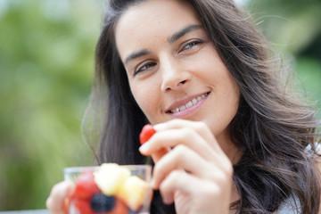 Brunette girl eating fresh fruits