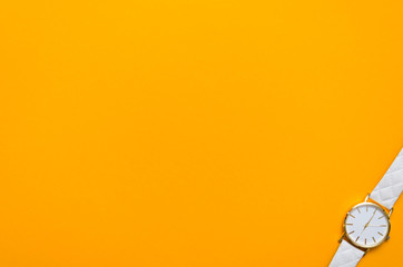Whigte pocket watch in the corner of an orange background
