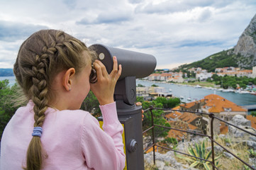 Little girl using coin operated panoramic telescope.
