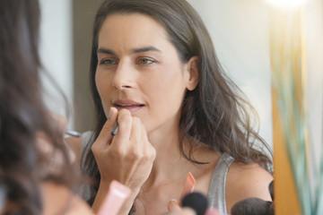 Brunette woman in front of mirror applying lipstik on