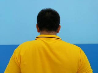 Back of a man with yellow polo and blue wall in the background
