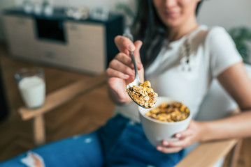 Close-up image of woman holding bowl of cereal and a spoon. Focus on the spoon.