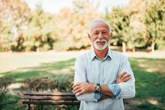 Portrait of a smiling older man in the park.
