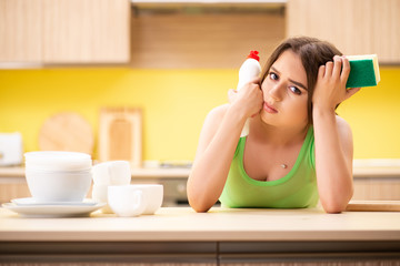 Young woman cleaning and washing dishes in kitchen