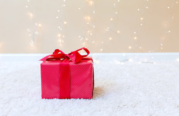 Christmas gift box on a carpet over a shiny light background