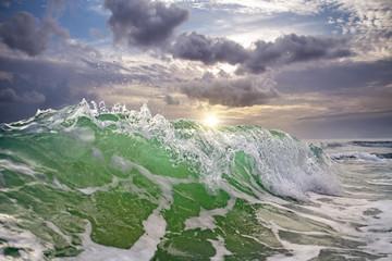 ocean wave against a sunset