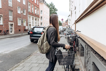 Tourist or student with a backpack is going to ride a bike.