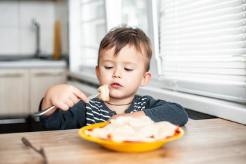 Hungry child eating dumplings in the kitchen, sitting at the table in a gray jacket