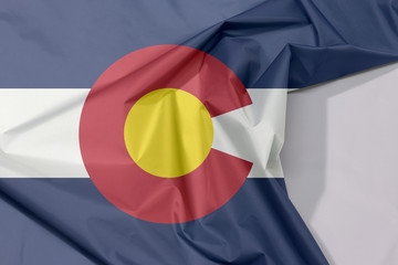 "Colorado fabric flag crepe and crease with white space, The states of America, blue white and blue. On top of these stripes sits a circular red ""C"", filled with a golden disk."