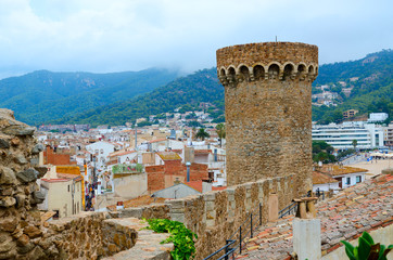 Old tower and stone walls against background of resort town of Tossa de Mar and mountains, Costa Brava, Spain