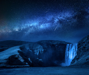 Fototapete - Milky way and falling stars over Skogafoss waterfall in Iceland
