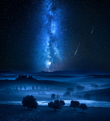 Milky way and falling stars over valley in Tuscany, Italy