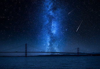 Fototapete - Milky way and falling stars over bay in Queensferry, Scotland