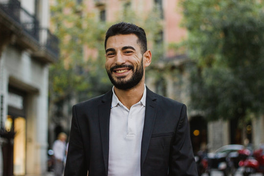 Handsome arabic guy smiling. Successful man walking on the street