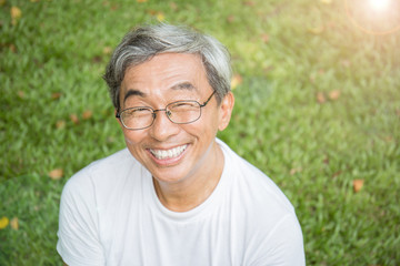 Portrait of healthy happy senior asian old man in the park outdoors with copy space. Spring healthcare lifestyle retirement concept