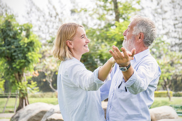 Happy old couple smiling dancing in a park on a sunny day, hoot senior couple relax in the forest spring summer time. Healthcare lifestyle retirement concept