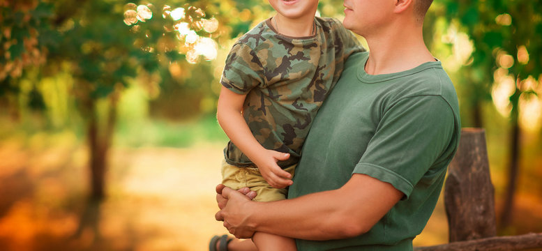 Portrait of happy son embracing a soldier