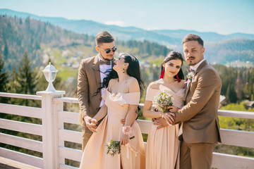 Portrait of a happy wedding guest couples laughing at camera. Bridesmaid and groomsmen outdoor portrait. Funny wedding moment. Before wedding ceremony.