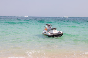 In the summer, white jet skis float in the blue sea. On a clear day.