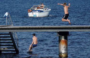 People enjoy warm autumn weather on a pier in Malmo