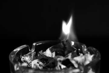 A piece of paper burning in a glass ashtray close up. Black and white
