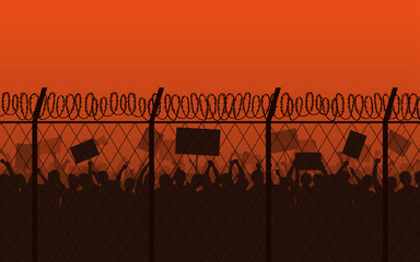 Silhouette group of people Raised Fist and Protest Signs at evening with barbed wire fence and orange color sky background